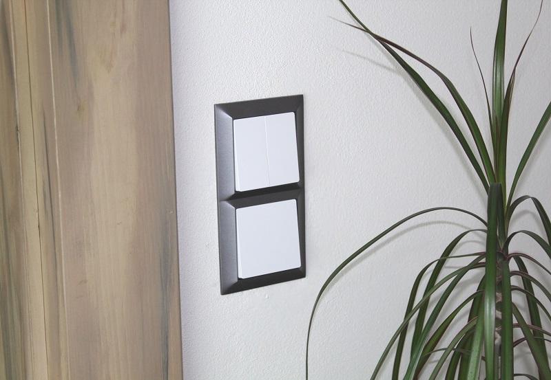 Bílý vypínač v šedém grafit rámečku
