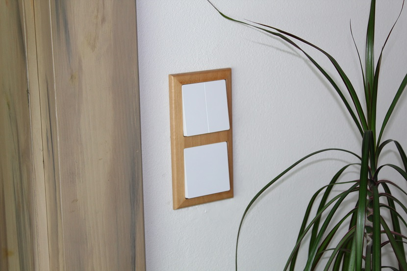 Bílé vypínače v dřevěném rámečku
