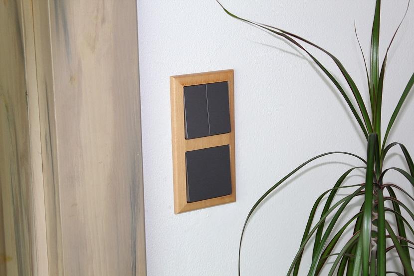Šedé vypínače v dřevěném rámečku